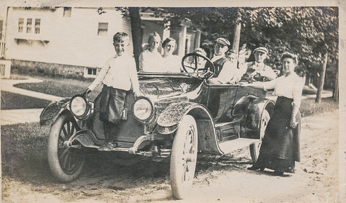 Family posing with their dirty car